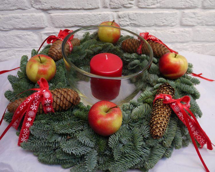 Adventsgesteck mit Windlicht und Äpfeln dekoriert