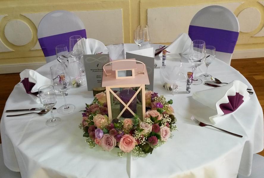 Blumendekoration für runde Tische, Windlicht und Blumengesteck als Kranz