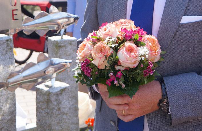 Bräutigam wartet auf die Braut mit kleinem Brautstrauss, Strauss mit Rosen und Bartnelken