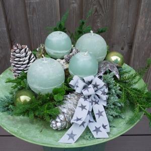 Adventsdekoration im skandinavischen Stil mit mintfarbenen Kugelkerzen, gefrosteten Zapfen und silberfarbenem Adventsschmuck