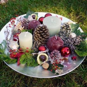 Eine vorweihnachtliche Kombination aus dunkelroten und graugrünen, gegossenen Vollwachskerzen, arrangiert auf einem silber leuchtenden Teller mit winterlichen, naturhaften Accessoires, dunkelrote und graugrüe Vollwachskerzen