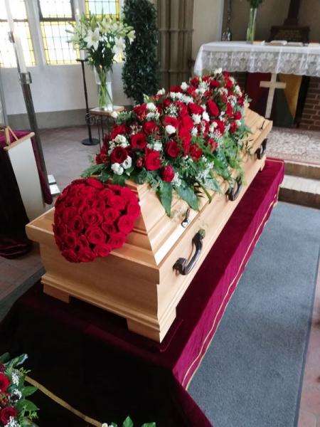 Blumenschmuck aus roten Rosen für den Sarg und ein Blumengebinde in Herzform ganz aus roten Rosen