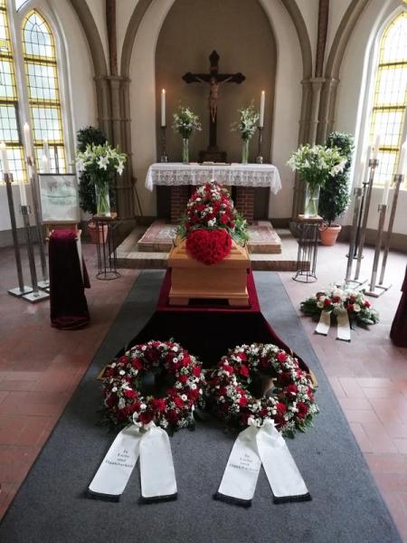 rot-weiße Trauerfloristik mit Rosen