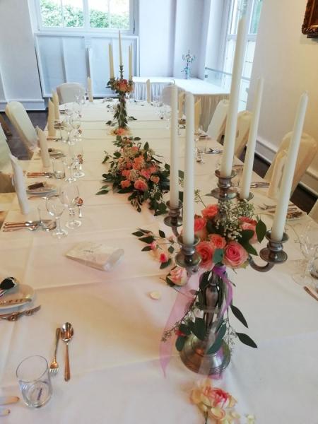 Blumendekoration für die festliche Tafel, mit zarten Rosen in Rosé und Pastell