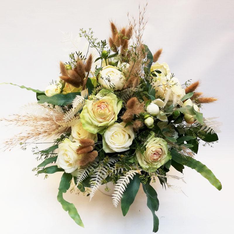 Blumenstrauß im Boho-Style, rund gebunden mit braunem Samtgras, creme-grünlichen Rosen, Lisianthus, Gräsern und grünem Blattwerk