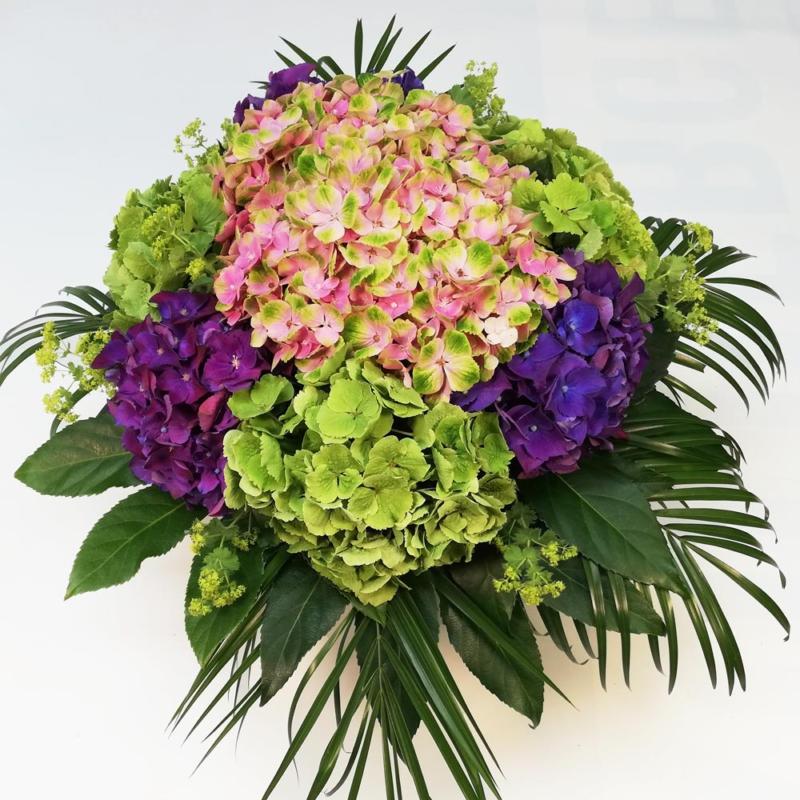 großer Hortensienstrauß, rund gebunden, gestaltet mit großen Blütendolden in Violett, Rosa-Grün und Grün, gerahmt von frischem Blattwerk