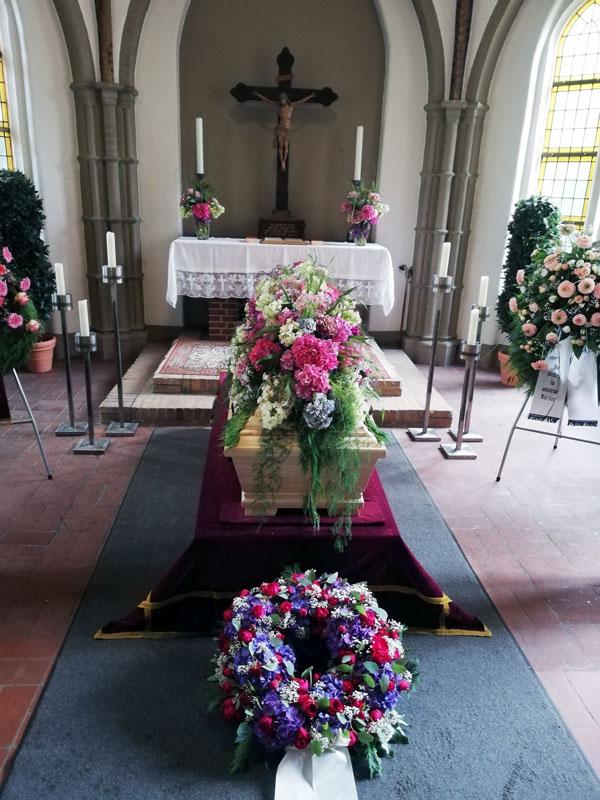 große Hortensienblüten in Rosé, Weiß, Pink und Blau als Blumendecke für den Sarg gearbeitet, davor ein Blumenkranz mit weißer Trauerschleife