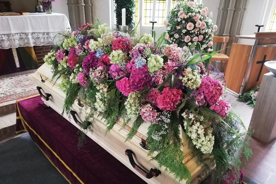 große Hortensienblüten in Rose, Weiß, Pink und Blau als Blumendecke für den Sarg gearbeitet