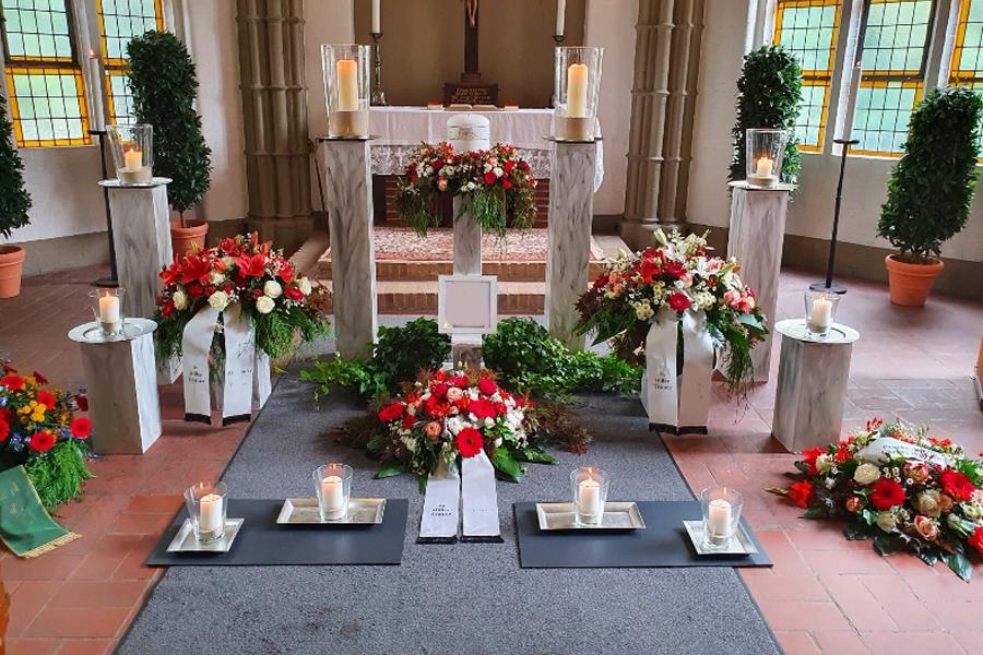 Trauerblumen in Rot und Weiß gestaltet, Gestecke und Urnenkranz in der Kapelle