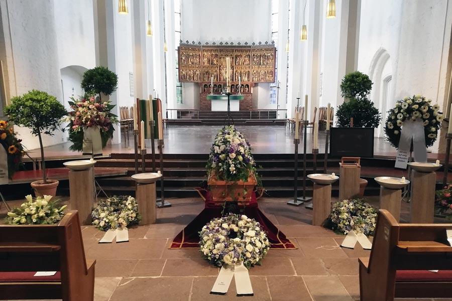 Blumenschmuck für Trauerfeier in der Kirche, Kränze und Sargschmuck aus weißen, fliederfarbenen und violetten Blüten